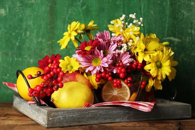 Composizione con crisantemo e frutta su legno