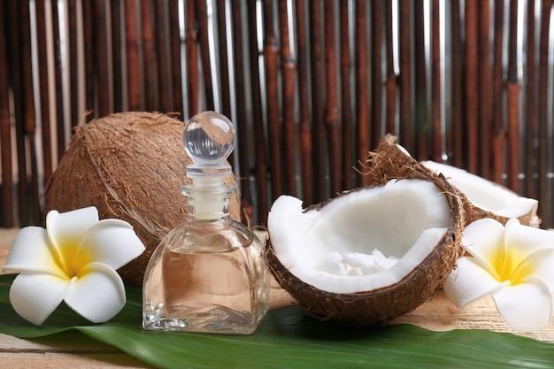 Composizione con olio di cocco in bottiglia per cure termali su foglia di palma