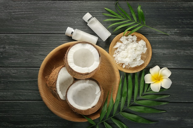Composizione con noci di cocco e olio su tavola di legno