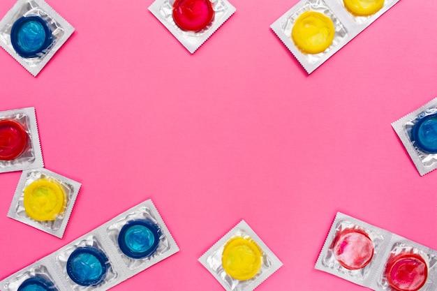 Composizione con preservativi colorati sulla superficie rosa brillante