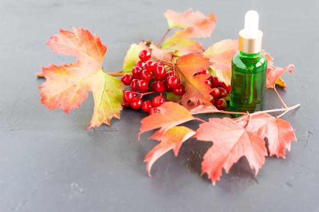 Composizione con un flacone cosmetico di vetro verde con olio di viburno e un ramo con bacche rosse su sfondo nero.