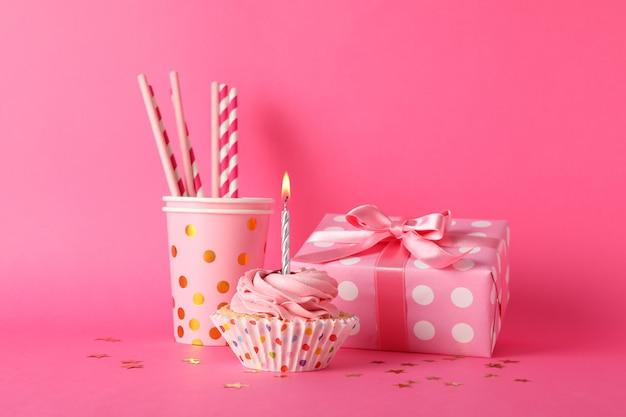 Composizione con cupcake e confezione regalo su sfondo rosa, spazio per il testo