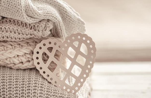 Composizione con un cuore decorativo sullo sfondo di vestiti caldi ordinatamente piegati. concetto di san valentino.