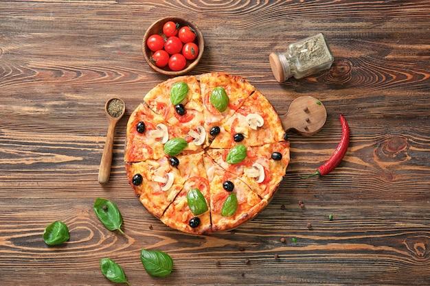 Composizione con una deliziosa pizza italiana su una superficie di legno