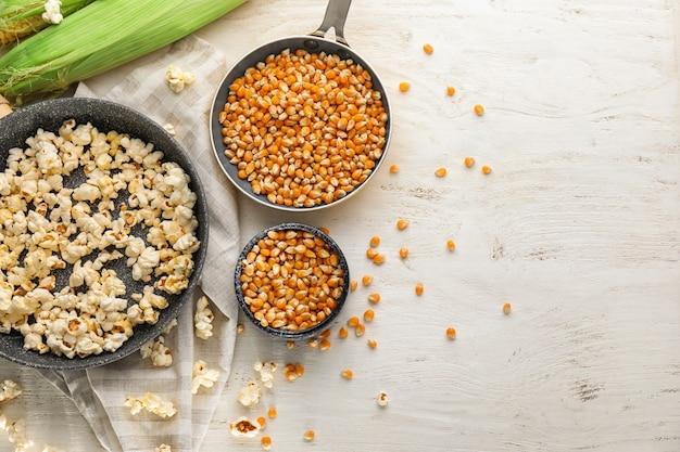 Composizione con deliziosi popcorn e noccioli sul tavolo di legno