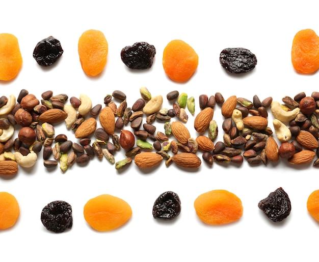 Composizione con diverse noci e frutta secca su sfondo bianco