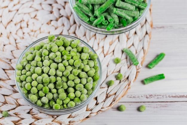 Composizione con diverse verdure surgelate biologiche su fondo di legno bianco. fagiolini e piselli in una ciotola