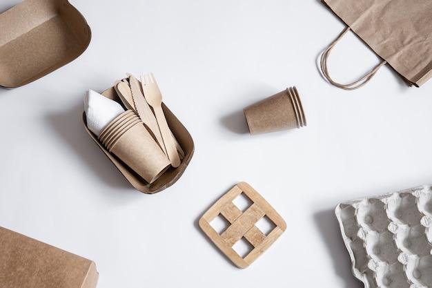 Composizione con stoviglie ecologiche usa e getta e altre parti in carta. lay piatto