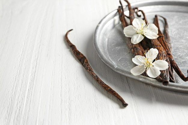 Composizione con bastoncini di vaniglia secchi sulla tavola di legno chiaro, primo piano