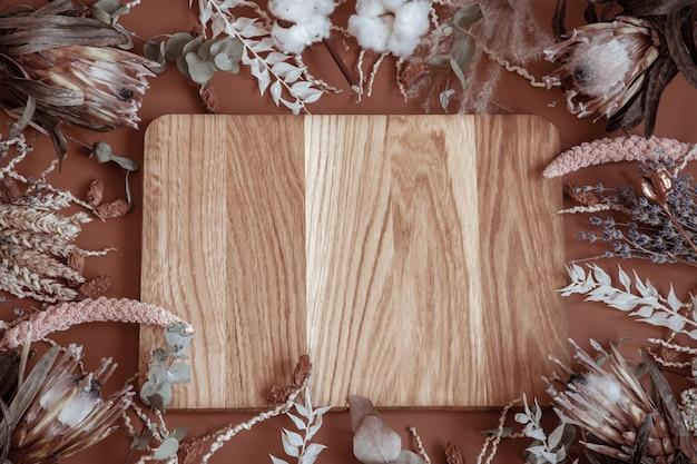 Composizione con fiori di campo essiccati, spighette, fiori di protea e al centro un elemento in legno