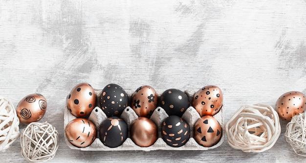 Composizione con uova di pasqua dipinte nei colori oro e nero con ornamenti