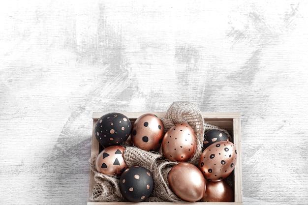 Composizione con uova di pasqua dipinte in oro e nero su luce.