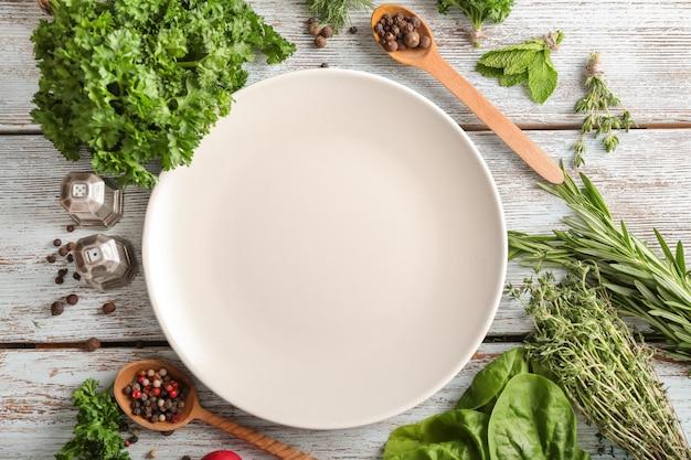 Composizione con piatto vuoto, diverse erbe fresche e spezie su tavola di legno