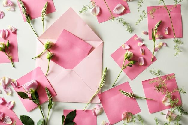 Composizione con fiori, busta e carte su bianco