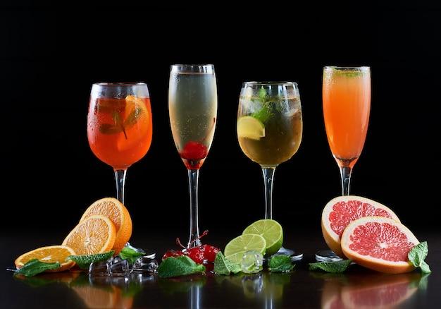 Composizione con quattro bicchieri da cocktail in cristallo di diverse forme con bevande fredde, fette di arancia, lime e pompelmo, cubetti di ghiaccio fondenti, foglie di menta e ciliegie rosse