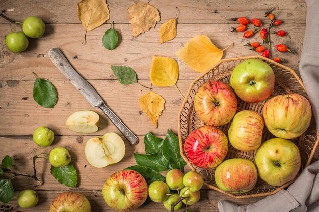 Composizione con mele fresche sulla vecchia tavola di legno