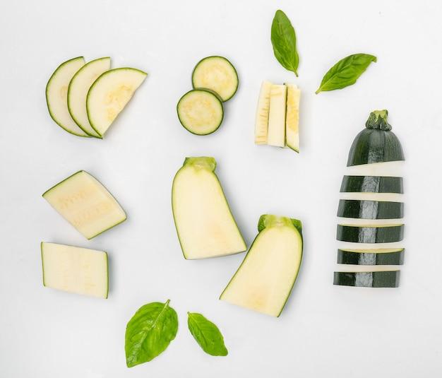 Composizione con zucchine fresche tagliate su bianco