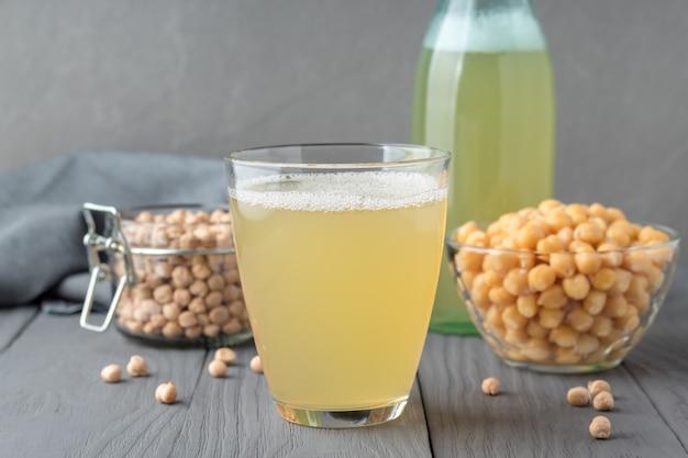 Composizione con bicchiere di aquafaba e ceci su tavolo in legno grigio