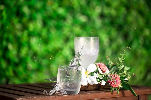 Composizione con un bicchiere di acqua fredda e fiori tropicali. sete estiva e concetto di bevanda fredda.