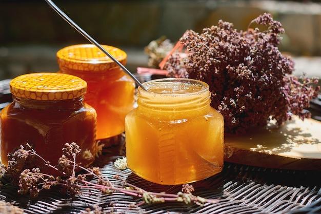 Composizione con vasetti di vetro di miele in piedi su un tavolo di vimini, un concetto di sana alimentazione
