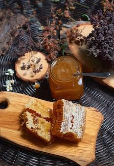 Composizione con vasetti di vetro di miele in piedi su un tavolo di vimini, corteccia di albero, concetto di mangiare sano, vista dall'alto