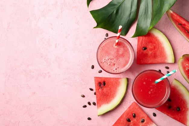 Composizione con bicchiere di succo di anguria e fette sul tavolo rosa