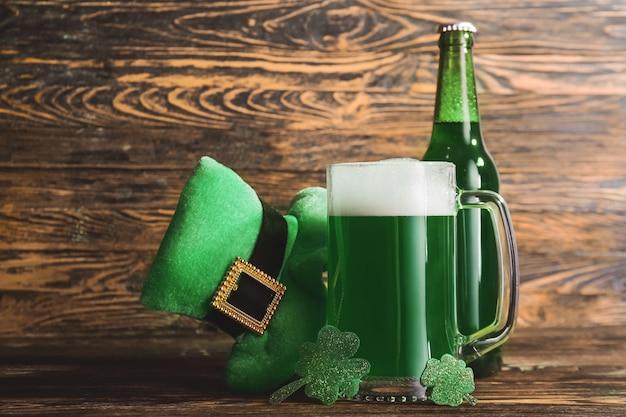 Composizione con birra verde per il giorno di san patrizio su tavola di legno