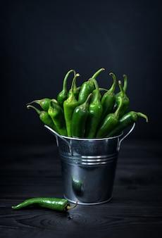Composizione con peperoncino verde sulla tavola di legno