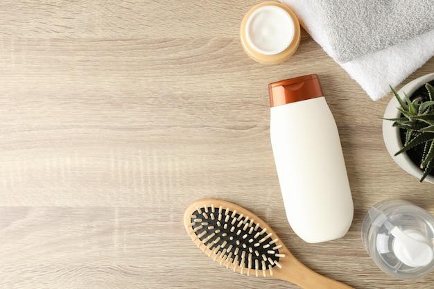 Composizione con prodotti per la cura dei capelli su fondo in legno, vista dall'alto
