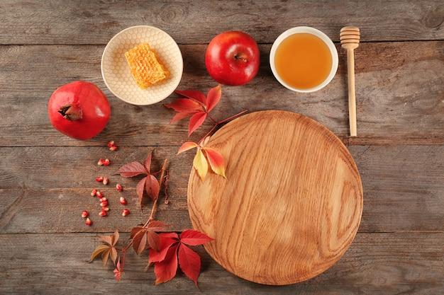 Composizione con miele, mela e melograno per le vacanze di rosh hashanah su tavola di legno, vista dall'alto