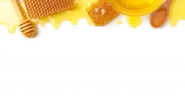 Composizione con favi, miele e mestolo su sfondo bianco