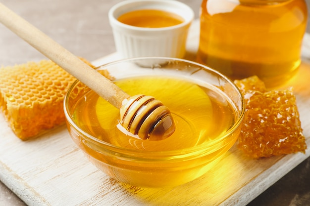 Composizione con favi, miele, barattoli e mestolo sul tavolo grigio