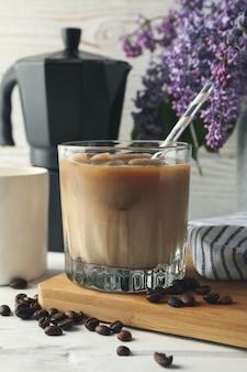 Composizione con caffè di ghiaccio e fiori su bianco in legno