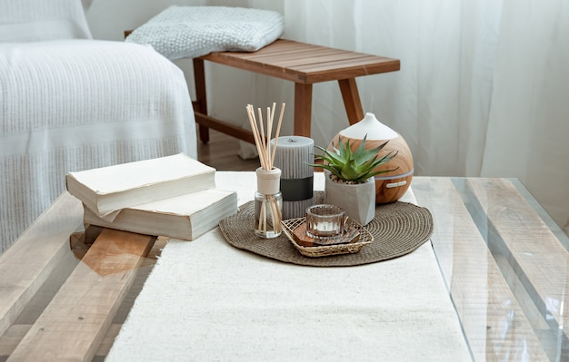 Composizione con bastoncini d'incenso, diffusore, candele e libri sul tavolo all'interno della stanza.
