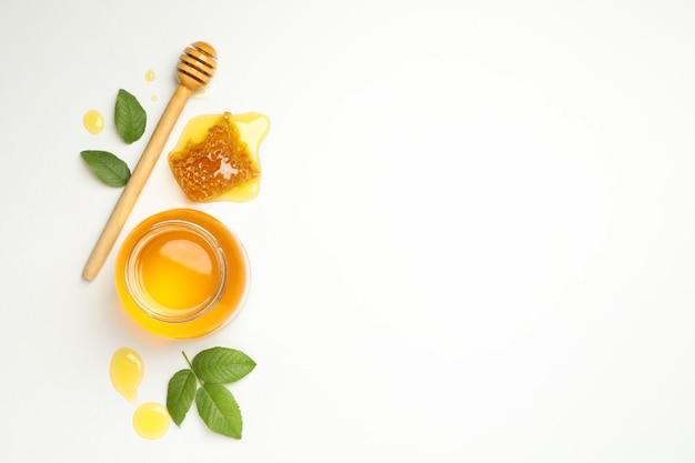 Composizione con vasetto di miele, foglie e mestolo su sfondo bianco