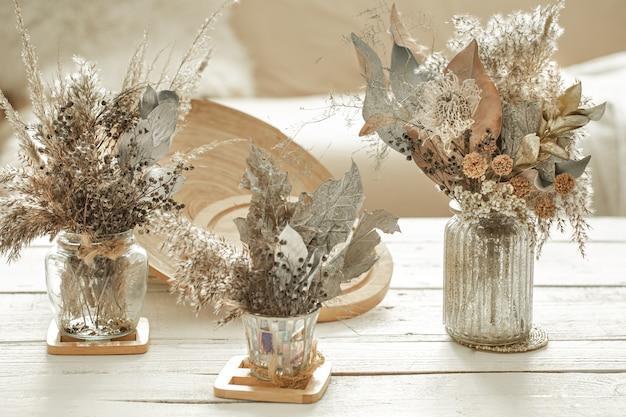 Composizione con molti fiori secchi in vasi.
