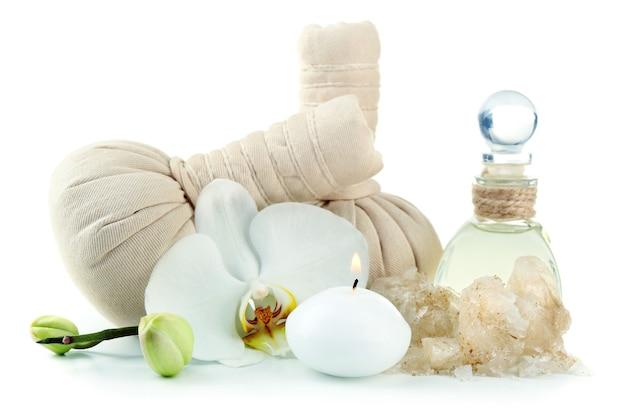 Composizione con borse da massaggio, sale marino e fiori di orchidea, su fondo bianco