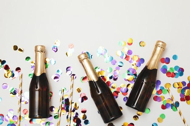 Composizione con mini bottiglie di champagne e glitter su spazio bianco, copia spazio