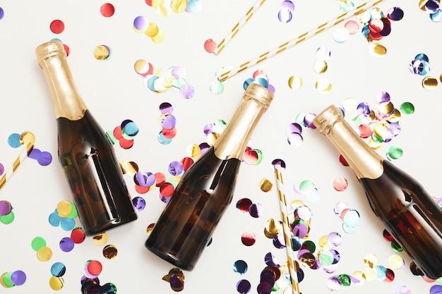 Composizione con mini bottiglie di champagne e glitter su spazio bianco, vista dall'alto