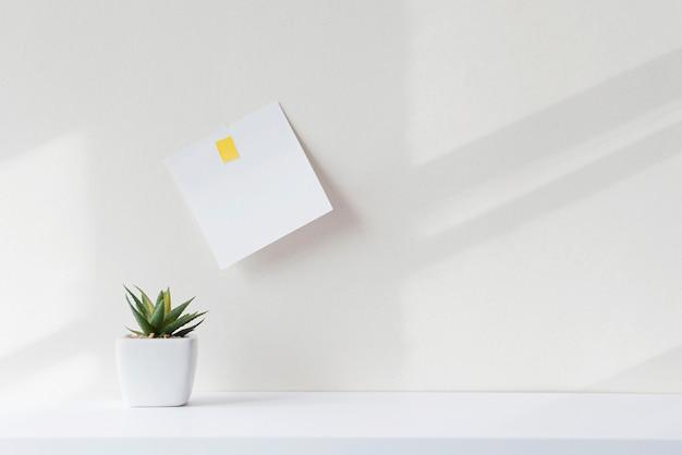Composizione con oggetti minimali su scrivania bianca. nota quadrata di carta bianca sul tavolo in ufficio. interni con ombre astratte durante la giornata di sole.