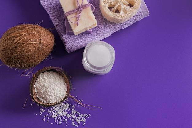 Composizione con crema corpo cosmetica all'olio di cocco biologico naturale su sfondo di colore viola