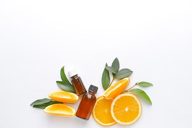 Composizione con olio essenziale di arancia su superficie bianca