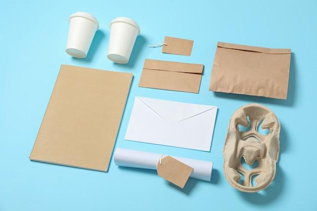 Composizione con bicchieri di carta e articoli per ufficio su sfondo blu, copia spazio