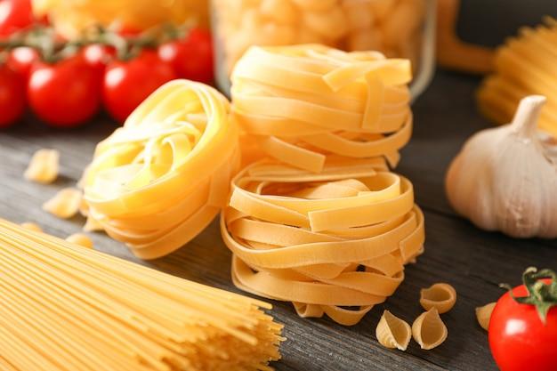 Composizione con pasta che cucina gli ingredienti sulla tavola di legno, spazio per testo e primo piano
