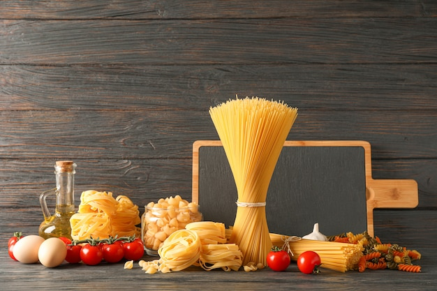 Composizione con pasta che cucina gli ingredienti sulla tavola di legno, spazio per testo