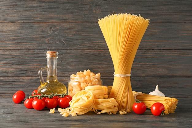 Composizione con pasta, olio d'oliva, pomodori e aglio sul tavolo di legno, spazio per il testo