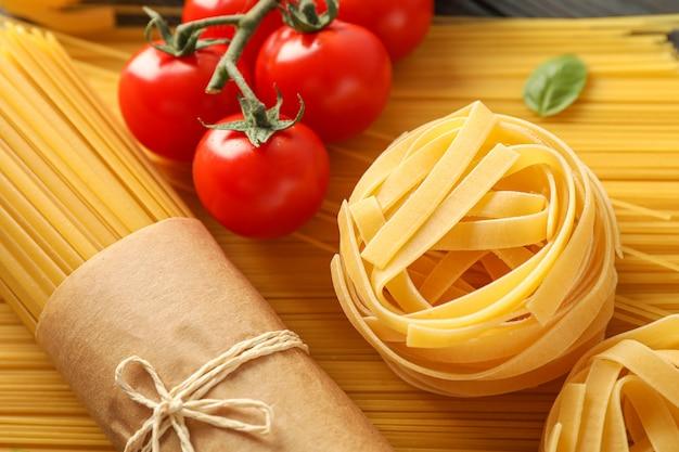Composizione con pasta, i pomodori e il basilico su fondo di legno, primo piano