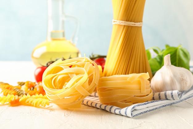 Composizione con pasta, pomodori, aglio, olio d'oliva e asciugamano da cucina su fondo bianco, spazio per testo e primo piano