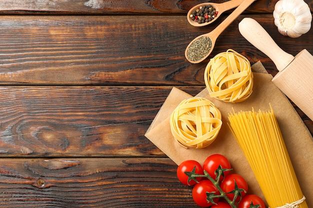Composizione con pasta, pomodori, mattarello, aglio e spezie su fondo di legno, spazio per il testo