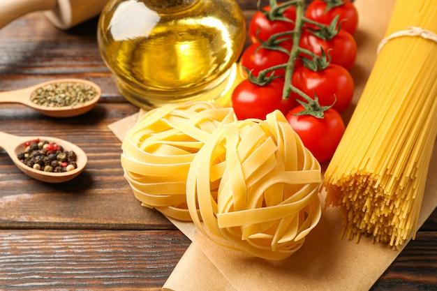 Composizione con pasta, pomodori, matterello, spezie e olio d'oliva su fondo di legno, spazio per testo e primo piano